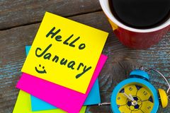Hello January - handwriting in black ink on a sticky note with a. Cup of coffee and alarm clock , New Year resolutions concept Stock Photos