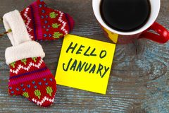 Hello January - handwriting in black ink on a sticky note with a. Cup of coffee and mittens, New Year resolutions concept Royalty Free Stock Image