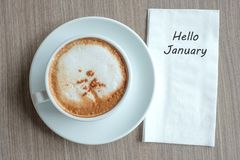 Hello January word with hot cappuccino coffee cup on table background at the morning. New Year New Start, Resolution, Solution,. Strategy and Mission concept stock images