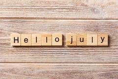 Hello juli ord som är skriftligt på träsnittet hälsningjuli text på tabellen, begrepp Royaltyfria Bilder