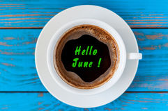 Hello June text on morning cup of coffee at blue wooden background Stock Image