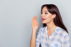 Hello, listen here! Portrait with copy space of half turned caucasian, charming, pretty, cute woman in checkered shirt holding ha royalty free stock images