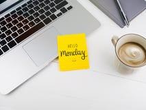 Hello måndag text med smileyframsidan på klibbig anmärkning på skrivbordet arkivfoto