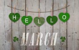 Hello Maart bij het hangen van groene harten en doorstane houten achtergrond wordt geschreven die stock fotografie