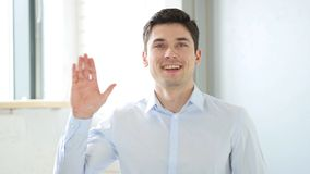 Hello by Man in Office, Indoor Waving Hand. High quality Stock Photos