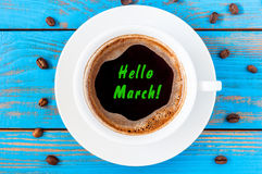 Hello MARCH concept. Text on top viewed morning coffee mug at blue wooden background. Spring begin Royalty Free Stock Photography