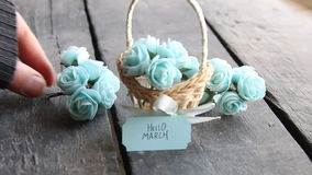 Hello March - decorative lettering card. Rustic still life, roses. Hello March. Label and beautiful basket of roses on vintage table stock footage