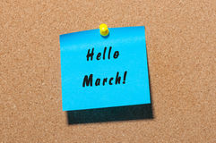 Hello March - handwriting on a blue paper pinned at cork noticeboard. Beginning of spring concept.  Royalty Free Stock Photo