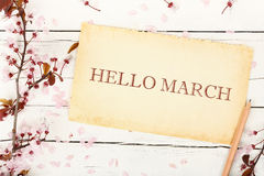 Hello march. Written on aged paper with almond tree twig on white wood Stock Photo