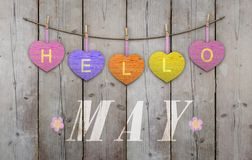Hello May written on hanging pink and orange and purple hearts and weathered wooden background stock photography