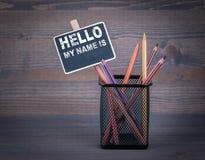 Hello is mijn naam Een klein bordkrijt en een kleurpotlood op houten achtergrond stock fotografie