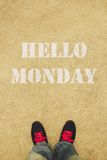 Hello Monday. Text is painted on the ground in front of the feet royalty free stock images