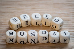 Hello monday. Text on a wooden cubes on a wooden table stock photography
