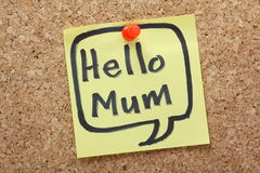 Hello Mum. The phrase Hello Mum in a speech bubble written by hand in felt tip on a yellow sticky note and pinned to a cork notice board Royalty Free Stock Photography