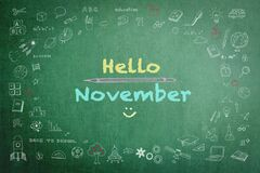 Hello November greeting on green school chalkboard with doodle