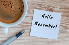 Hello November. hand drawn lettering on notepad at the table with morning coffee cup. Top view Royalty Free Stock Image