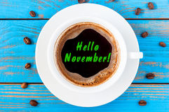 Hello November written on coffee cup at blue wooden surface. Autumn time concept, Top view Stock Photos