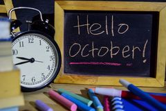 Hello october on phrase colorful handwritten on blackboard. Education and business concept. Alarm clock, chalk, books on black background stock photo