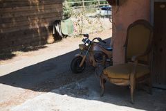 Hello from past. Traditional old stables. The old broken brown and yellow chair is standing behind the wall near the old yellow children`s motorcycle Stock Photography