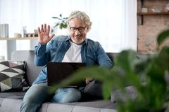 Happy senior male using laptop for communication. Hello. Portrait of cheerful mature man speaking with someone by internet. He is waving arm to computer screen Royalty Free Stock Image