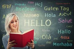 Hello. Pretty girl holding a red book in front of a huge blackboard written with the word hello in different languages and colors. Opportunity for learning many stock image