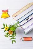 Hello September Böcker, bokmärkeexponeringsglas, pepparkakablyertspenna och gul klocka, krysantemum på en vit bakgrund royaltyfria foton