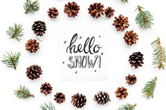 Hello snow hand lettering. Winter pattern with pinecones and spruce branch on white background top view Royalty Free Stock Photo