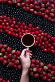 Hello sommar En kopp av svart kaffe i en kvinnlig hand på en svart bakgrund med sommarbär: jordgubbar vinbär royaltyfria foton
