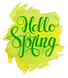 Hello Spring lettering on yellow green watercolor stroke. stock photos