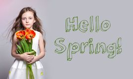 Hello Spring, 8 march. Fashion red-haired girl with tulips in hands. Studio photo on light coloured background. Spring day stock image