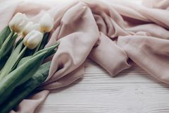 Hello spring. stylish white tulips on beige soft fabric on rustic wooden table background. soft light, tenderness atmospheric mom. Ent. space for text. rustic stock photos