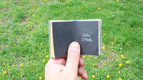 Hello spring. Text in a book on the background of grass and flowers stock video footage
