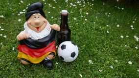 Hello Summer ! A funny garden gnome with a flag, a football and a bottle of beer sits happily on a green meadow. Happy holidays ! A funny garden gnome sits on a royalty free stock photo