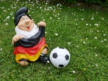 Hello Summer ! A funny garden gnome with a flag and a football sits happily on a green meadow. Happy holidays ! A funny garden gnome sits on a green meadow This royalty free stock photography