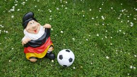 Hello Summer ! A funny garden gnome with a flag and a football sits happily on a green meadow. Happy holidays ! A funny garden gnome sits on a green meadow This stock photography