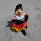 Hello Summer ! A funny garden gnome with a flag sits happily on a pile of sand at the beach. Happy holidays ! A funny garden gnome sits at the beach This photo royalty free stock images
