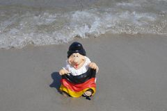 Hello Summer ! Funny garden gnome with a germany flag sits happily on a pile of sand at the beach with the sea in the back. Happy holidays ! A funny garden gnome royalty free stock photos