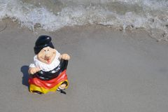 Hello Summer ! Funny garden gnome with a germany flag sits happily on a pile of sand at the beach with the sea in the back. Happy holidays ! A funny garden gnome stock photos
