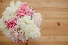 Hello summer. Happy mothers day greeting card. Beautiful peonies in vase and petals on rustic wooden table top view with space for. Text. International Women`s stock photos