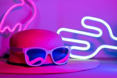 Hello Summer with hat and sunglasses refection flamingo neon light with cactus on  pink and blue light on table with copy space. stock photos