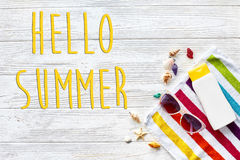 Hello summer text on  colorful towel, sunglasses, yellow sunscre Stock Photo