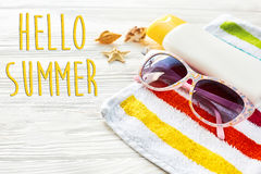 Hello summer text on colorful towel, sunglasses, yellow sunscree Stock Image