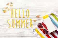 Hello summer text on colorful towel, sunglasses, yellow sunscree Stock Images