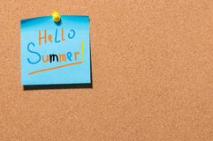 Hello Summer - text on little blue paper pinned to cork board background. First summer day, Calendar concept. With copy. Space for text royalty free stock photos