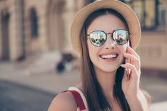 Hello from summer! Young pretty tourist is talikg on the mobile, wearing sunglasses and hat, smiling stock photo