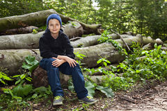 Hello!. A teenage boy sitting on some large tree trunks, relaxing looking friendly Stock Image