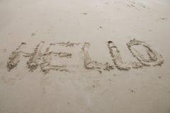 Hello-tekenwoord die op de zandachtergrond trekken Stock Foto's