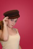 Hello There!!. Young beautiful female tipping wool vintage cap to viewer Royalty Free Stock Photos