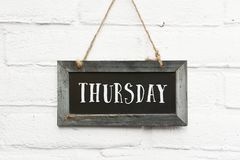 Hello thursday text on hanging board white brick ourdoor wall. Hello thursday text on hanging chalkboard with wooden frame against white brick ourdoor wall royalty free stock image