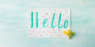 Hello uttrycker stavning vid blommor för guling för vattenfärghandbokstäver Arkivfoton